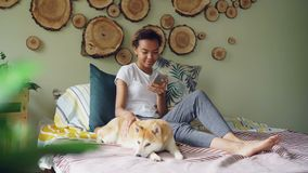 Pretty young woman is using smartphone and caressing lovely puppy lying on bed near its owner in modern style bedroom at. Home. Technology, domestic animals and stock video footage