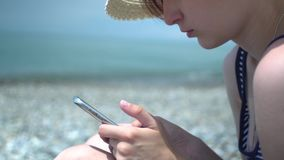 Pretty young woman using smartphone by the sea beach. Girl in retro hat and swimsuit with blue and white stripes stock video