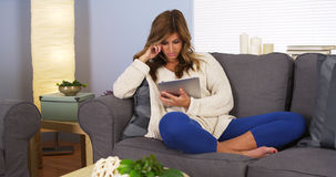 Pretty young woman using tablet computer in living room Royalty Free Stock Images