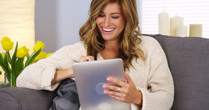 Pretty young woman using tablet computer in living room Royalty Free Stock Photography