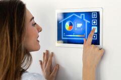Pretty Young Woman Using The Home Automation System On Digital Tablet To Regulate The Temperature Royalty Free Stock Photos