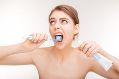 Pretty young woman using toothpaste and brushing her teeth Stock Images