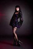 Pretty young woman in Victorian purple and black Halloween outfit. And high heels royalty free stock photography