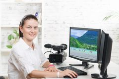 Pretty young woman video editor. With computer and professionnal video camera stock photo