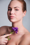 Pretty young woman with violet iris flower Royalty Free Stock Photo