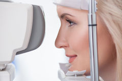 Pretty young woman is visiting eye doctor. Cheerful blond girl is looking into eye test machine with concentration in oculist lab. She is smiling stock photos