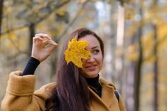 Pretty Young Woman Walking in Autumn Park Leaves Fall Relax Leisure Fashion Modern. Golden Yellow Coat Long Hair royalty free stock photos