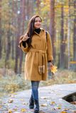 Pretty Young Woman Walking in Autumn Park Leaves Fall Relax Leisure Fashion Modern. Golden Yellow Coat Long Hair royalty free stock image