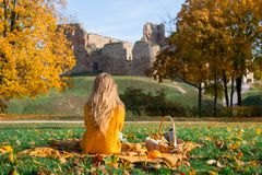 Pretty Young Woman Walking in Autumn Park Leaves Fall Relax Leisure. Fashion Modern Golden Yellow Coat Long Hair royalty free stock image