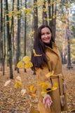 Pretty Young Woman Walking in Autumn Park Leaves Fall Relax Leisure Fashion Modern. Golden Yellow Coat Long Hair royalty free stock images