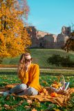 Pretty Young Woman Walking in Autumn Park Leaves Fall Relax Leisure. Fashion Modern Golden Yellow Coat Long Hair royalty free stock photos