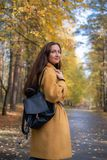 Pretty Young Woman Walking in Autumn Park Leaves Fall Relax Leisure Fashion Modern. Golden Yellow Coat Long Hair stock images