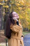 Pretty Young Woman Walking in Autumn Park Talking on Phone Mobile Leaves Fall Relax. Leisure Golden Yellow Coat Long Hair Casual Style Emotions on Face royalty free stock images