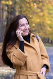 Pretty Young Woman Walking in Autumn Park Talking on Phone Mobile Leaves Fall Relax. Leisure Golden Yellow Coat Long Hair Casual Style Emotions on Face stock photos
