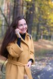 Pretty Young Woman Walking in Autumn Park Talking on Phone Mobile Leaves Fall Relax. Leisure Golden Yellow Coat Long Hair Casual Style Emotions on Face stock images