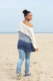 Pretty young woman walking on the beach and looking over shoulder Royalty Free Stock Image
