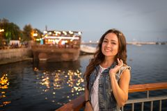 Pretty young woman walking on city promenade near sea in the evening. Soft colors. Street lights rays falls on her face. Happy girl enjoys vacation royalty free stock photography
