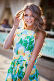 Pretty young woman walking in the city sunny evening. Happy and. Smilling girl. Long curly hair. Floral fashion dress Royalty Free Stock Photo
