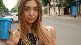 Beautiful Young Woman Walking in the City. Using her Mobile Phone. Typing a Message. Smiling Happily. Drinking Delicious. Pretty Young Woman Walking in the City stock video footage