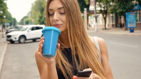 Beautiful Young Woman Walking in the City. Using her Mobile Phone. Typing a Message. Smiling Happily. Drinking Delicious. Pretty Young Woman Walking in the City stock video