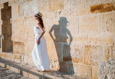 Pretty young woman walking near the stone wall Stock Image