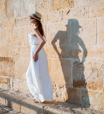 Pretty young woman walking near the stone wall Royalty Free Stock Images