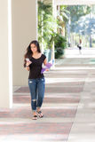 Pretty young woman walking outdoors texting on smart phone Stock Image