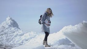 Pretty young woman in warm jacket walking on the glacier, holding her cellphone in raised hand, trying to find mobile. Portrait of young blond pretty woman in a stock video