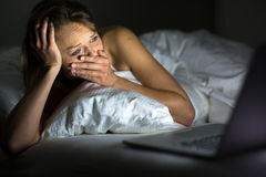 Pretty young woman watching something awful/sad on her laptop. In bed Stock Photography