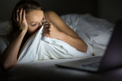 Pretty young woman watching something awful/sad. On her laptop in bed Royalty Free Stock Photo