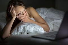 Pretty young woman watching something awful/sad. On her laptop in bed Stock Photo