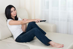 Pretty young woman watching tv Stock Image