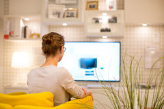 Pretty, young woman watching TV at home. (color toned image; shallow DOF Stock Images