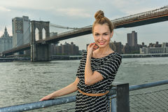 Pretty young woman at the waterfront location with Brooklyn Bridge on the background. Royalty Free Stock Image