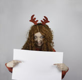 Pretty young woman wearing antlers and holding blank sign Stock Photos