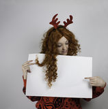 Pretty young woman wearing antlers and holding blank sign Royalty Free Stock Images