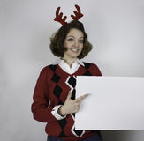 Pretty young woman wearing antlers and holding sign Stock Photo