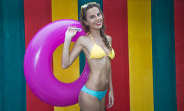 Pretty young woman wearing bikini holding pink inflatable ring  on the colorful wall Royalty Free Stock Images