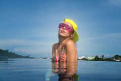 Pretty young woman wearing bikini, yellow hat and purple sunglas. Ses posing in infinity rooftop pool on a sunny day over blue sky and green trees landscape Royalty Free Stock Image