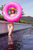 Pretty young woman wearing bikini. Yellow hat and purple sunglasses with pink inflatable ring posing in infinity rooftop pool on a sunny day over blue sky and Royalty Free Stock Photo
