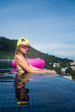 Pretty young woman wearing bikini. Yellow hat and purple sunglasses with pink inflatable ring posing in infinity rooftop pool on a sunny day over blue sky and Stock Images