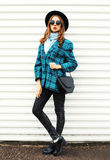 Pretty young woman wearing fashion black hat checkered coat jacket handbag walking in city over white Stock Image