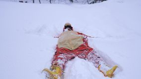 Pretty young woman wearing funny tiger suit lying in snowdrift in winter and throwing up snow during snowfall. slow stock video footage