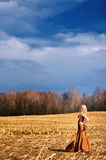 Pretty young woman wearing a gown in a field Stock Photos