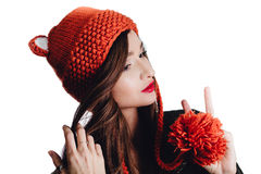 Pretty young woman wearing a hand knitted red hat on white background. Isolated. Beautiful girl in with Ear flap. Stock Images