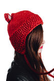 Pretty young woman wearing a hand knitted red hat on white background. Isolated. Beautiful girl in with Ear flap. Stock Photography
