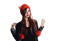 Pretty young woman wearing a hand knitted red hat on white background. Isolated. Beautiful girl in with Ear flap. Royalty Free Stock Photo