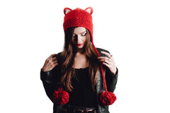 Pretty young woman wearing a hand knitted red hat on white background. Isolated. Beautiful girl in with Ear flap. Royalty Free Stock Image