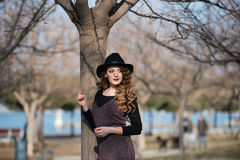 Pretty young woman wearing hat lean on a tree Stock Photos