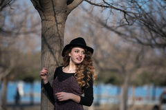Pretty young woman wearing hat lean on a tree Royalty Free Stock Photo